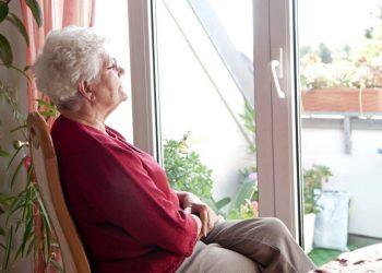самотня стара жінка сидить біля вікна